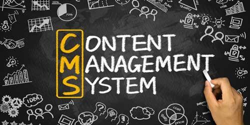 """Sort tavle med symboler der omkranser hovedbudskabet """"Content Management System"""". Neders ses en hånd der holder et stykke kridt ved teksten."""